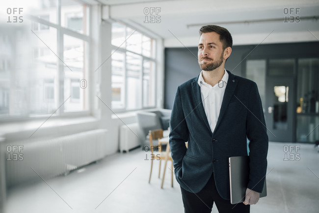 Businessman holding laptop in office