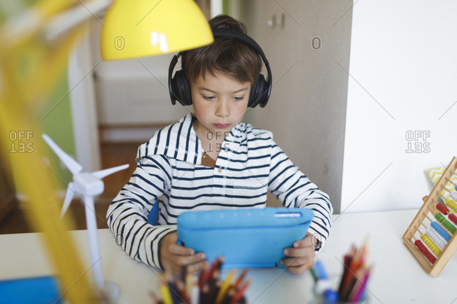Boy doing homeschooling and using tablet and headphones at home