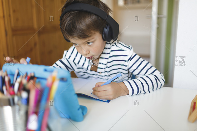 Boy doing homeschooling and writing on notebook- using tablet and headphones at home