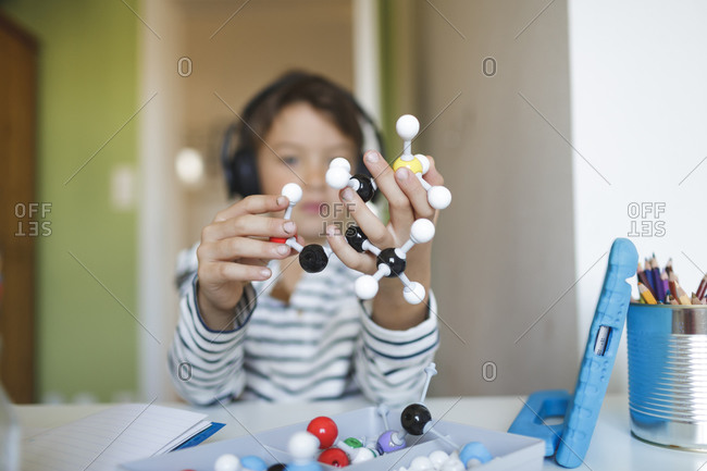Boy doing homeschooling and holding molecule model- using tablet and headphones at home