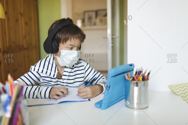 Boy doing homeschooling and writing on notebook- using tablet and headphones- wearing mask at home during corona crisis