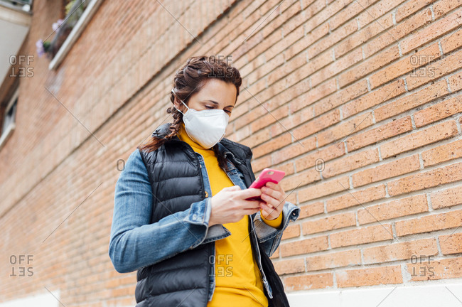 Woman covering her face with protective mask and using smartphone