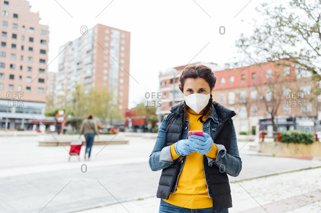 Woman wearing protective mask and using smartphone on square