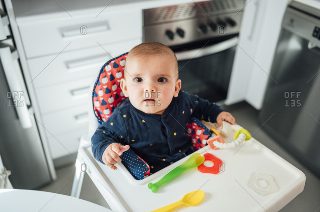 Portrait of staring baby boy sitting on high chair