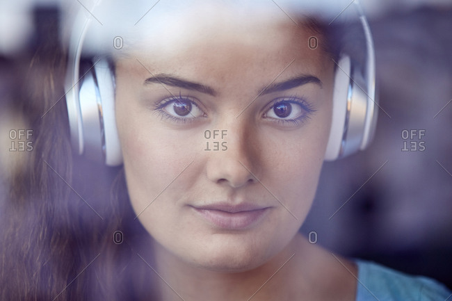 Portrait of young woman behind windowpane listening music with headphones