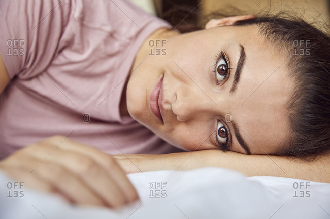 Portrait of young woman with brown eyes lying on bed