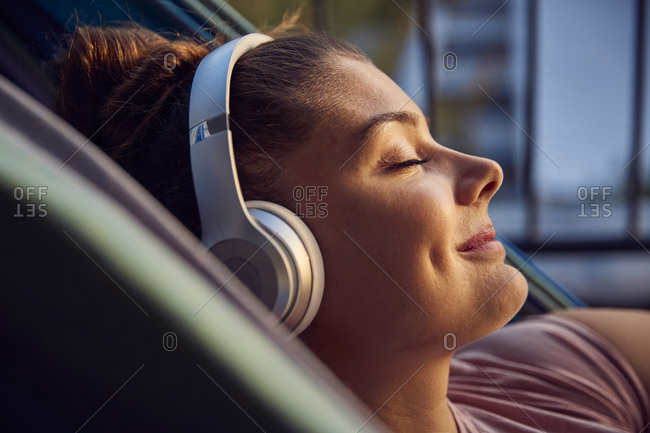 Smiling young woman lying on hammock on balcony listening music with headphones