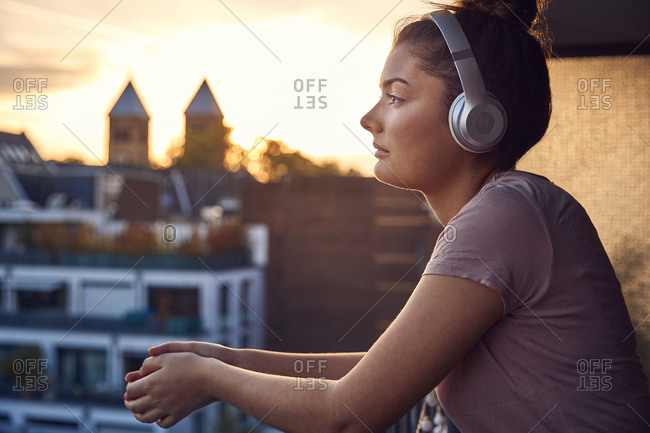 Young woman listening music with headphones on balcony at sunset