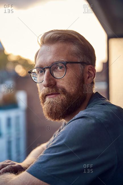Portrait of bearded man on balcony at dusk