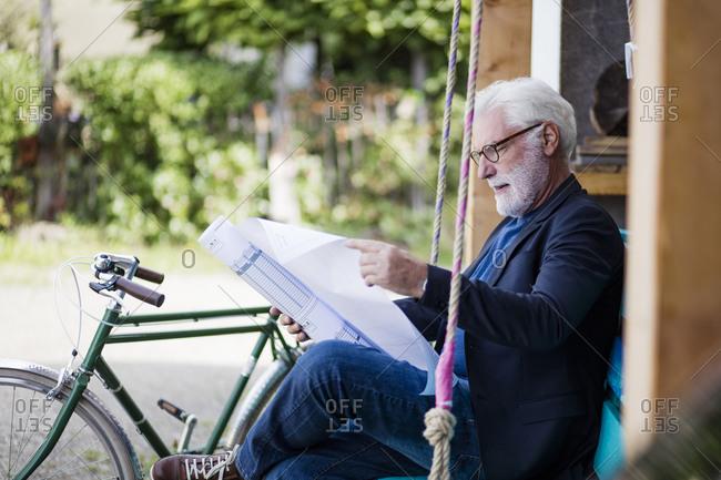Senior man sitting outdoors looking at construction plan