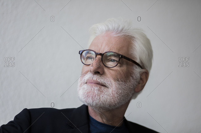 Portrait of bearded senior man with white hair looking at distance