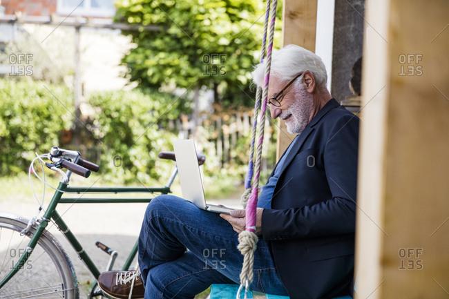 Senior man sitting outdoors looking at laptop