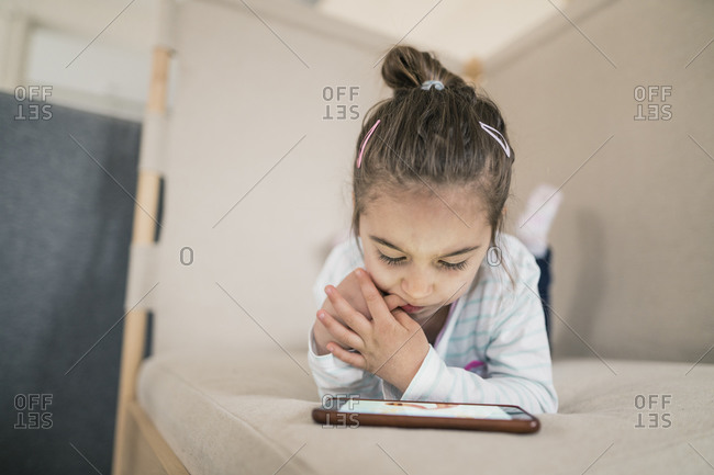 Little girl lying down looking at smartphone