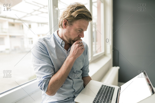 Casual businessman using laptop at the window