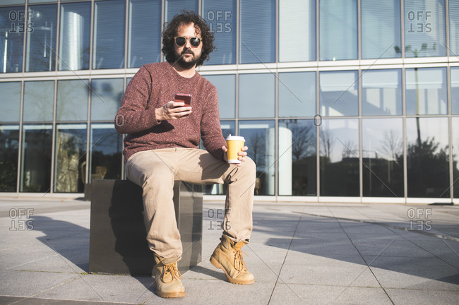 Portrait of bearded man sitting outdoors with coffee to go and smartphone