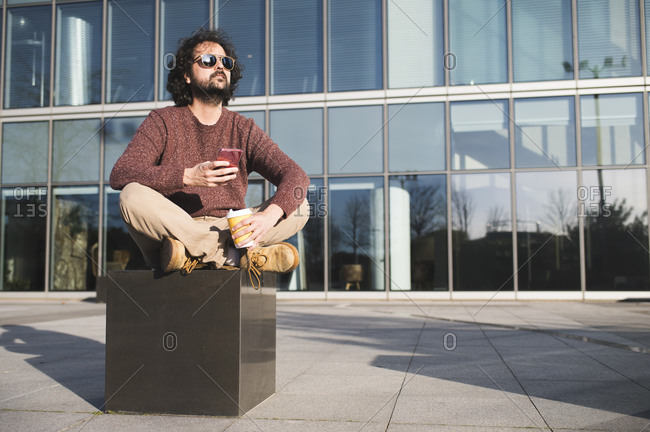 Portrait of bearded man sitting outdoors with coffee to go and smartphone enjoying sunlight