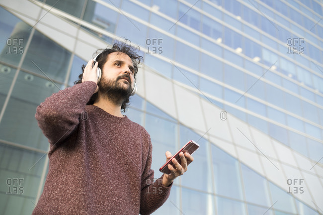 Portrait of bearded man with headphones and smartphone outdoors looking at distance