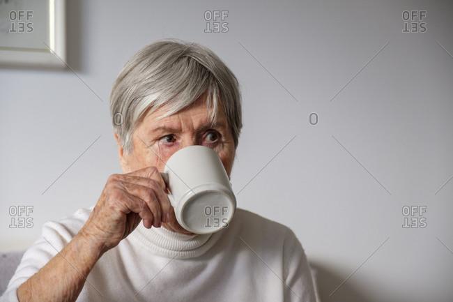 Portrait of senior woman drinking tea at home