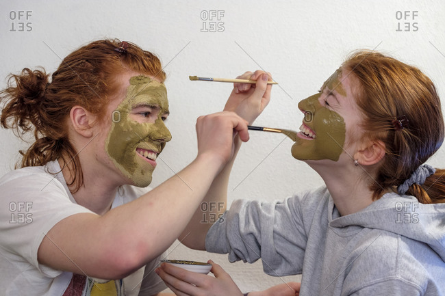 Brother and sister applying facial mask having fun