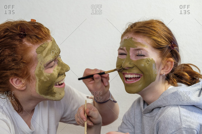 Brother applying facial mask on his sister's face
