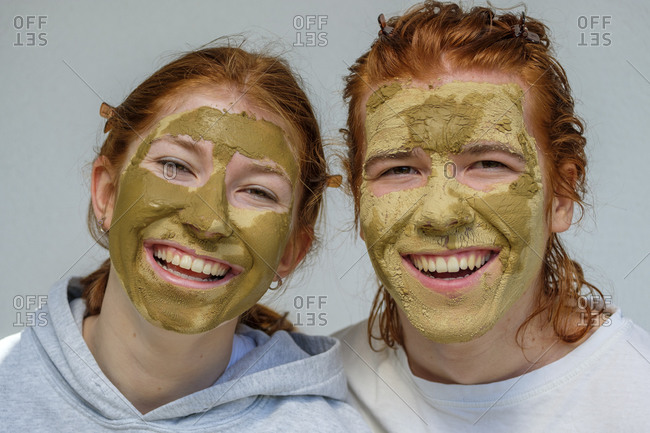 Portrait of laughing brother and sister with facial masks