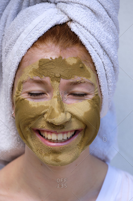 Portrait of laughing teenage girl with facial mask