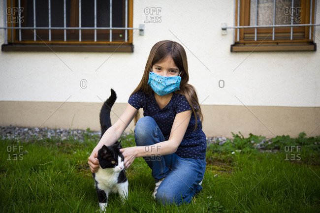 Girl wearing protective mask and stroking her cat in garden