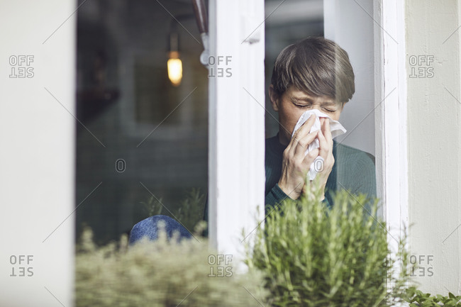 Woman blowing her nose at home at the window