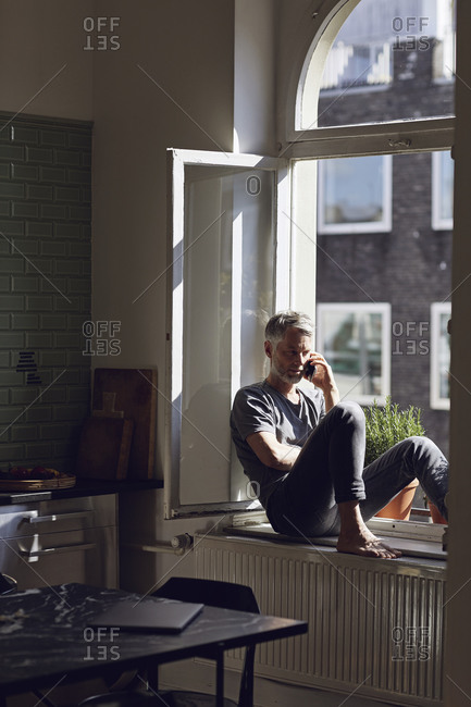 Mature man sitting at the window at home talking on the phone