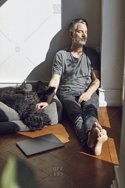 Mature man sitting on the floor at home with dog
