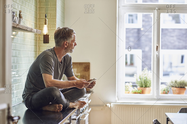 Mature man with cell phone sitting on kitchen counter at home