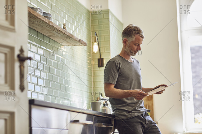 Mature man reading newspaper in kitchen at home