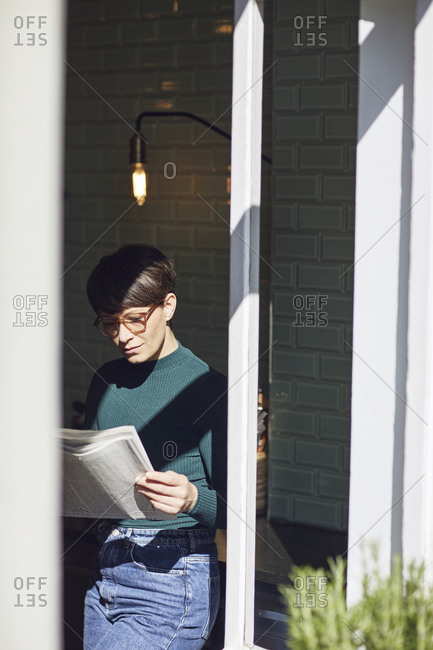 Woman standing at the window at home reading newspaper