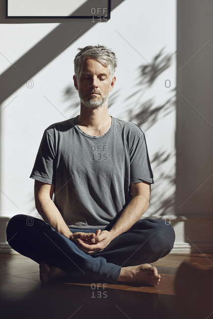 Mature man sitting on the floor at home meditating