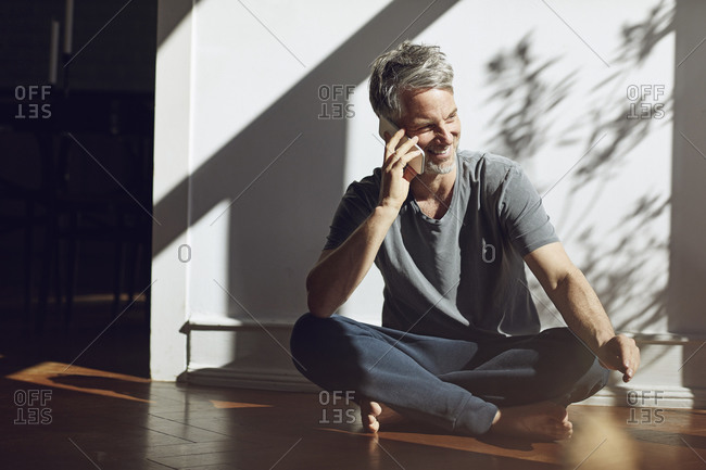 Smiling mature man sitting on the floor at home talking on the phone