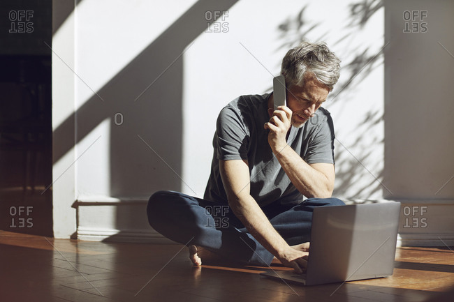 Mature man sitting on the floor at home using laptop and cell phone