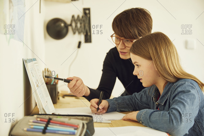 Mother helping daughter doing homework at home