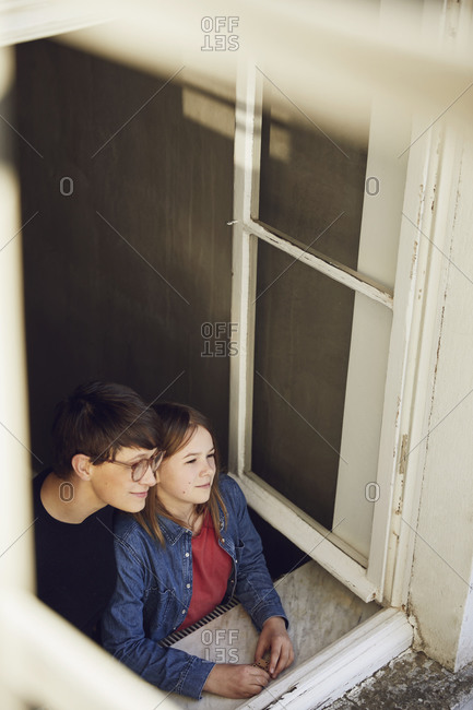 Mother and daughter at home looking out of window