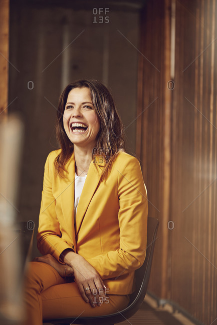 Laughing businesswoman wearing yellow suit sitting at desk in office
