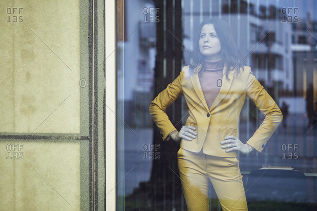 Confident businesswoman wearing yellow suit standing behind windowpane