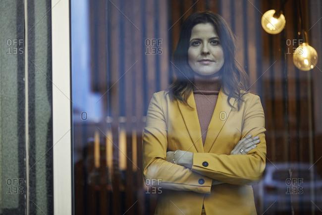 Portrait of confident businesswoman wearing yellow suit standing behind windowpane