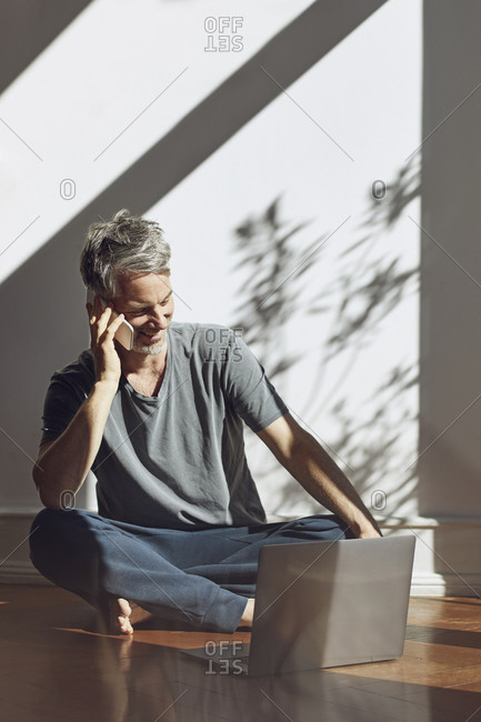 Mature man on the phone sitting on the floor at home with laptop