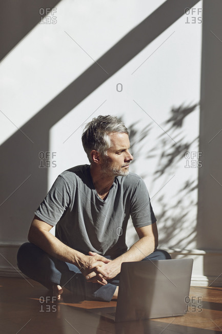 Mature man sitting on the floor with laptop looking at distance