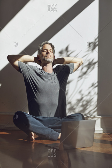 Mature man sitting on the floor at home relaxing