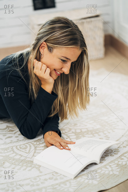 Woman lying on the floor at home reading a book