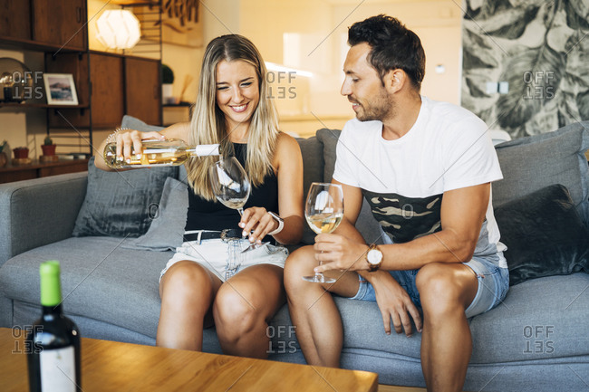 Couple sitting on the couch with glasses of white wine