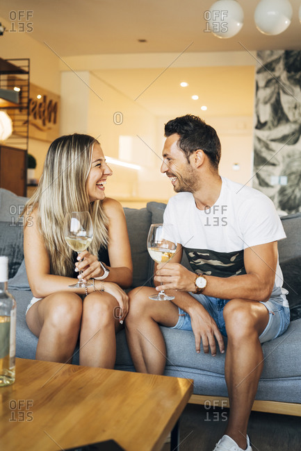 Laughing couple sitting on the couch with glasses of white wine