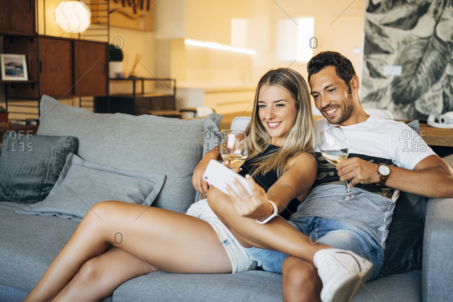Portrait of happy couple sitting on the couch with glasses of white wine taking selfie with smartphone