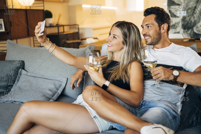 Happy couple sitting on the couch with glasses of white wine taking selfie with smartphone