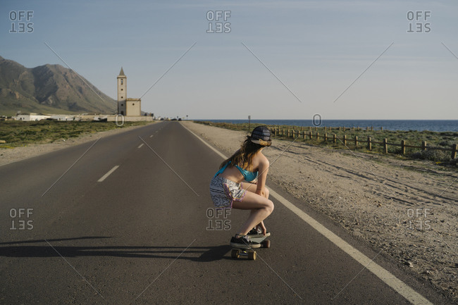 Back view of young woman skateboarding on asphalt road- Almeria- Spain